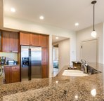 Kitchen with gleaming granite counter tops and stainless steel appliances.
