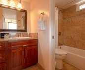Bathroom  vanity with wall to wall mirror and granite counters, plenty of cabinet storage.