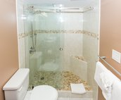 Walk in shower with glass doors and rain shower heads