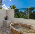 Enjoy this tropical en-suite shower and tub