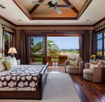 "Master bedroom with king bed, wall-mounted 52"" flat-screen TV, and sliding doors to private ocean-view lanai."