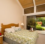 Master bedroom with king-size bed and lanai access.